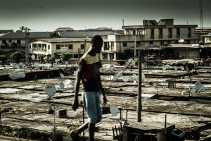 Young man in the streets of Lagos, with dozens of satellite dishes in the background on the rooftops